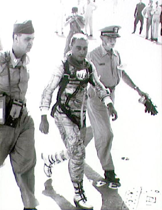 Astronautas Virgil Grissom, JAV lėktuvnešio Randolph denyje po suborbitinio skrydžio. Šalia - karo medikai